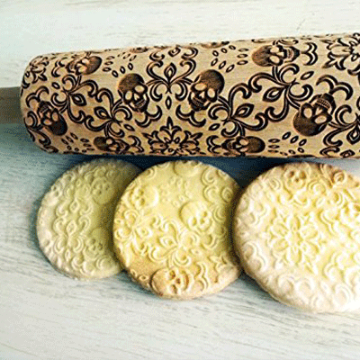 Handmade wooden rolling pin made from beech wood with laser-etched skull patterns on it.
